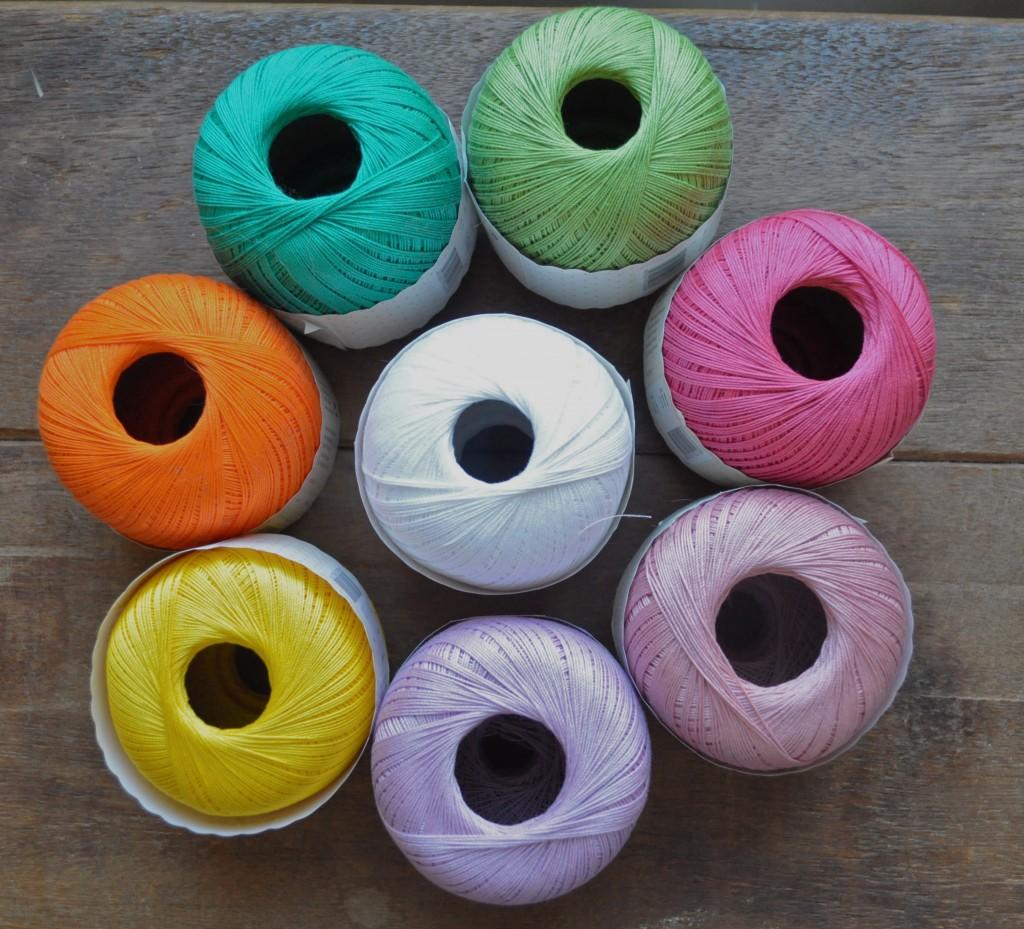 Rico Crochet Cotton. CW from Top - 009 Light Green, 005 Fushia, 016 Dusty Pink, 006 Lilac, 013 Yellow, 003 Orange, 008 Emerald. Centre- 001 White.